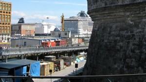 Vom Kreuzfahrtterminal gelangt man derzeit noch über einen Fußgängersteg in die Stadt. Er führt über die Baustelle, wo archäologische Funde in Kisten aufbewahrt werden. (© Redaktion Portanapoli.com)