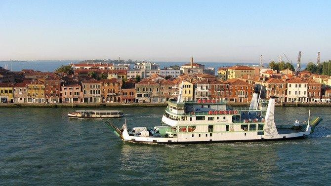 Ein Vaporetto fährt am Kreuzfahrtschiff vorbei