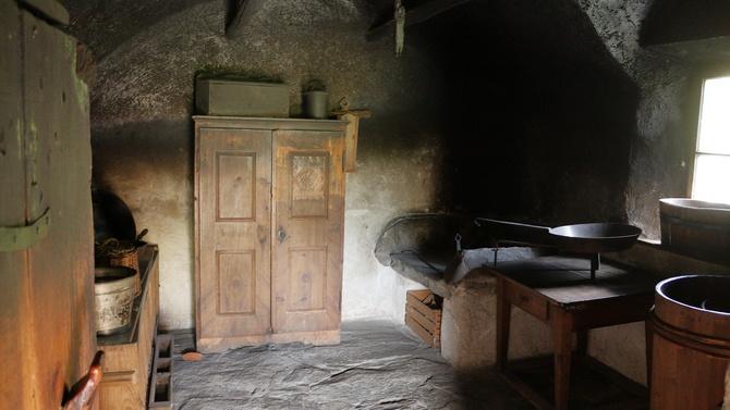 Über der Kochstelle ist die Wand schwarz vom Rauch, an der Decke hängt noch ein Stück Räucherwurst.