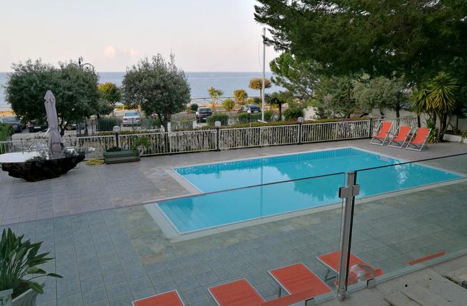 Blick von der Terrasse mit Olivenbäumen auf den Pool
